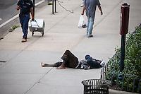 A homeless individual sleeps on the sidewalk in the Chelsea neighborhood of New York on Wednesday, July 3, 2016. (© Richard B. Levine)