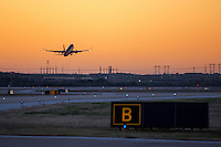 Jet airplane during takeoff with colorful sunrise at Austin Bergstrom International Airport ABIA, in Austin, Texas.