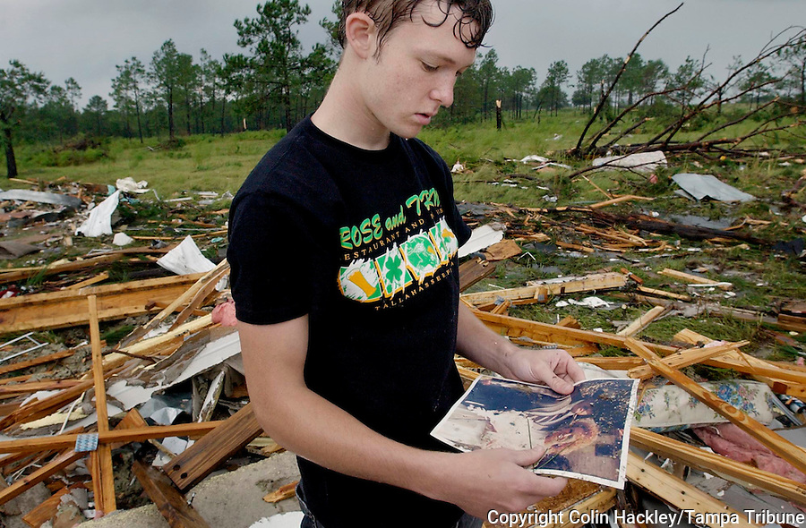BLOUNTSTOWN, FL. 9/16/04-Devon Rabon, age 19, holds a photo Thursday of his mother Mary and stepfather James Marshall who were killed late Wednesday after a tornado spawned by Hurricane Ivan destroyed their mobile home near Blountstown. Rabon, who stayed with his mother on weekends, was at the site Thursday recovering what he could from the wreckage of their home. COLIN HACKLEY PHOTO