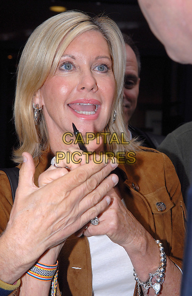 OLIVIA NEWTON-JOHN.Seen leaving BBC Radio 2 building in .London, England, UK, .September 30th 2009..half length mouth open brown jacket funny hand pen .CAP/IA.©Ian Allis/Capital Pictures.