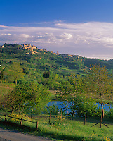 Tuscany, ITlay:  Morning sun on a green vallely with the hill town of Montepulciano on the distant hill top - Val d'Orcia area