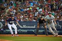 New Britain Rock Cats first baseman Jordan Patterson (9) holds Brodie Greene (8) on as umpire John Libka looks on during a game against the Reading Fightin Phils on August 7, 2015 at FirstEnergy Stadium in Reading, Pennsylvania.  Reading defeated New Britain 4-3 in ten innings.  (Mike Janes/Four Seam Images)