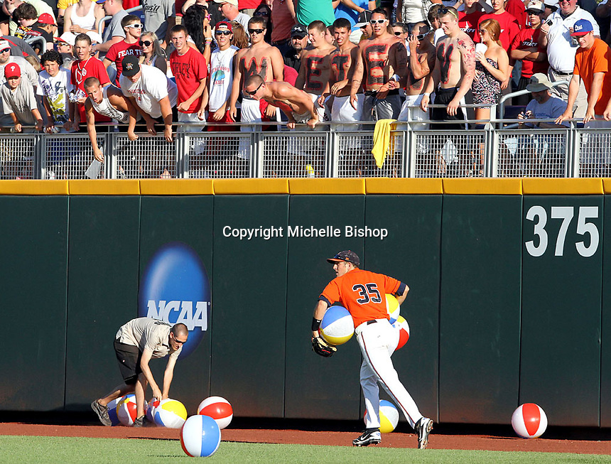 Virginia center fielder Kenny Swab (35) helps the TD Ameritrade Park grounds crew collect beach balls in the fourth inning. South Carolina beat Virginia 3-2 in 13 innings at the College World Series on June 24, 2011 in Omaha, Neb. (Photo by Michelle Bishop)..
