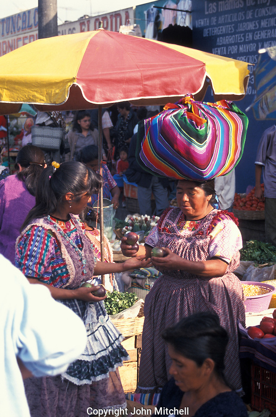 Young Maya woman selling apples to a customer in the market in Quetzaltenango, Guatemala
