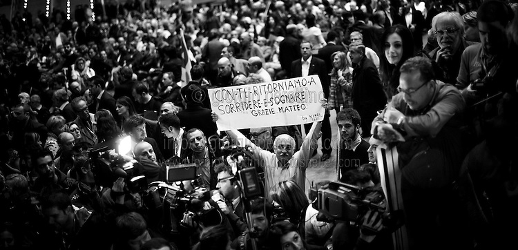 """A member of Partito Democratico - the Italian left-wing Party- holds a banner that reads """"We start again to smile and dream with you! Thanks Matteo"""" before the beginning of Matteo Renzi's speech during a political campaign convention for the Italian government elections in Turin, April 12, 2014."""