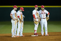 (L-R) Colin Rosenbaum (10), Josh Genthe (8), Matt McGarry (1), and Kayden Krause (13) of the Belmont Abbey Crusaders wait for the new pitcher to complete his warm-up tosses during the game against the Catawba Indians at Abbey Yard on February 7, 2017 in Belmont, North Carolina.  The Crusaders defeated the Indians 12-9.  (Brian Westerholt/Four Seam Images)