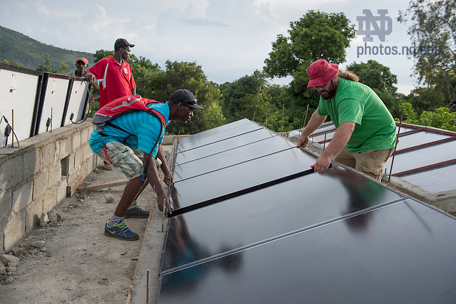 Aug. 11, 2015; Ken Oldrid and Longuisse, Simon set solar panels in place on the roof of St. Gabriel School in Fontaine, Haiti. (Photo by Barbara Johnston/University of Notre Dame)