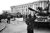 "ROMANIA, Pta. Palatului, today Pta. Revolutiei, Bucharest, 24.12.1989<br /> People rise against Ceausescu. The dictator has fled the city on dec. 22. At the central square intense figting with unidentifiable ""terrorists"" has been going on. Almost all buildings are damaged or partly destroyed. Army T-55 tanks.<br /> © Andrei Pandele / EST&OST"