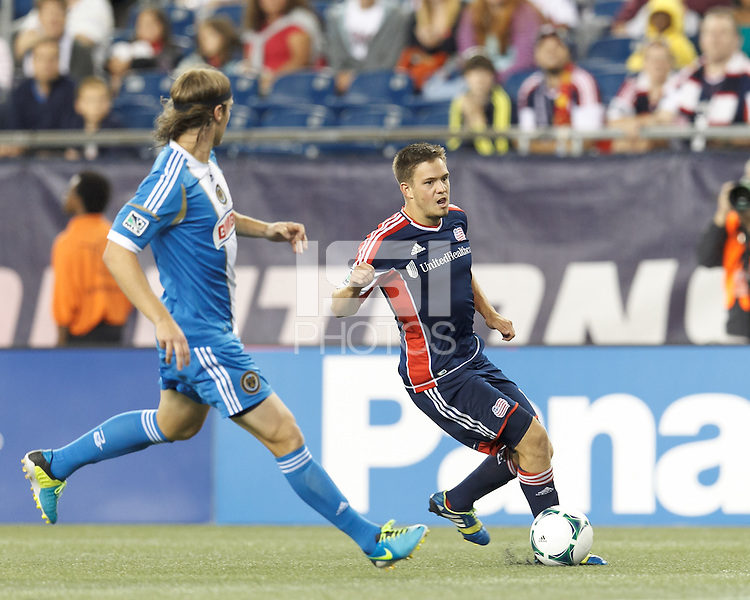New England Revolution midfielder Kelyn Rowe (11) on the attack.  In a Major League Soccer (MLS) match, the New England Revolution (dark blue) defeated Philadelphia Union (light blue), 5-1, at Gillette Stadium on August 25, 2013.
