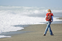 female tourist walking away from waves on isolated west coast beach near lake Mahinapua, New Zealand