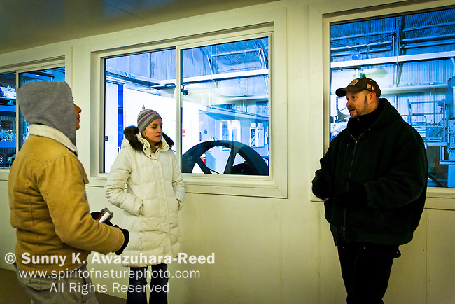 A tour guide showing the geothermal power plant, Chena Hot Springs Resort, Fairbanks, Interior Alaska. Model Released.