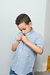 4 year old boy dressing self buttoning own shirt