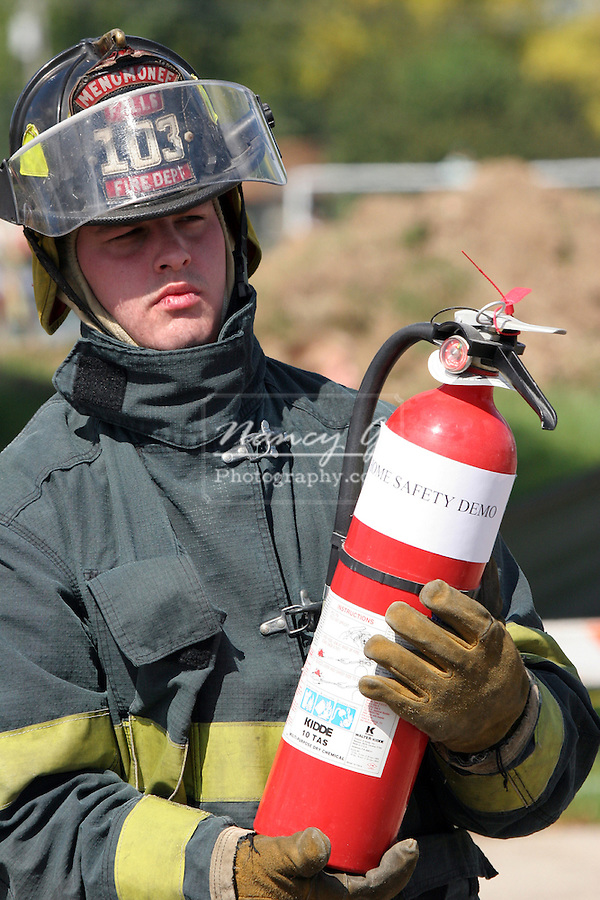 A firefighter holding an extinguisher that will be used in a demonstration at a fire safety fair