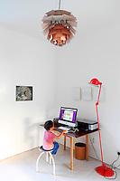A child sits at an Apple mac in his bedroom. A red retro style floor lamp sits beside a simple wood table.