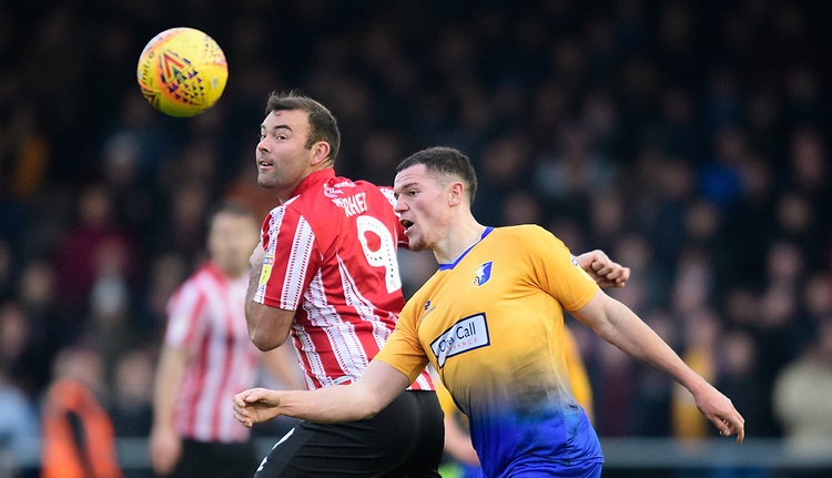 Lincoln City's Matt Rhead vies for possession with Mansfield Town's Matt Preston<br /> <br /> Photographer Chris Vaughan/CameraSport<br /> <br /> The EFL Sky Bet League Two - Lincoln City v Mansfield Town - Saturday 24th November 2018 - Sincil Bank - Lincoln<br /> <br /> World Copyright © 2018 CameraSport. All rights reserved. 43 Linden Ave. Countesthorpe. Leicester. England. LE8 5PG - Tel: +44 (0) 116 277 4147 - admin@camerasport.com - www.camerasport.com
