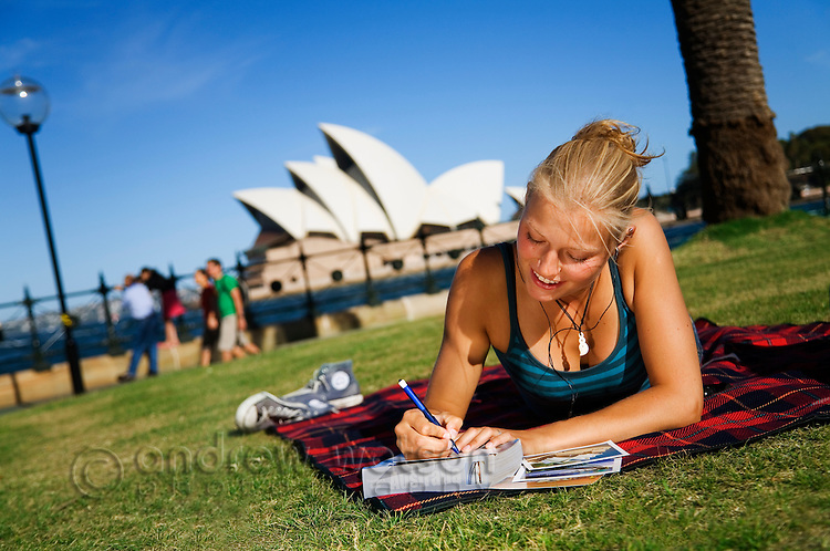 A young woman writes postcards at Dawes Point Reserve on Sydney harbour with the Opera House beyond.  Sydney, New South Wales, AUSTRALIA