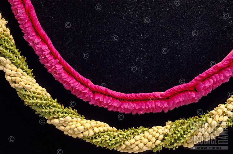 A pikake/pakalana and fuschia maunaloa orchid lei are stunning against a black background.