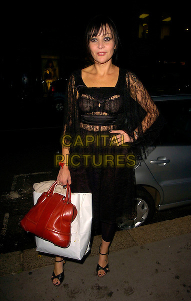 PEARL LOWE .The PPQ Mayfair flagship store opening party, Conduit Street, London, UK..September 18th 2006. .Ref: CAN.full length black lace dress bra orange bag purse goody hand on hip.www.capitalpictures.com.sales@capitalpictures.com.©Can Nguyen/Capital Pictures