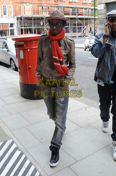 K'NAAN (Keinan Abdi Warsame).Seen outside outside BBC Radio 2, London, England, UK, May 10th 2010..full length red scarf hat sunglasses brown jacket leather jeans ripped denim walking hands in pockets black trainers .CAP/IA.©Ian Allis/Capital Pictures.