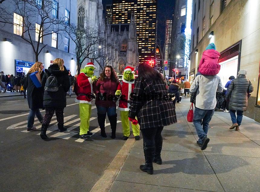 Als Grinch verkleidete Darsteller mit Touristen am Weihnachtsbaum und an der Eislauffläche vor dem Rockefeller Center in New York - 08.12.2019: New York