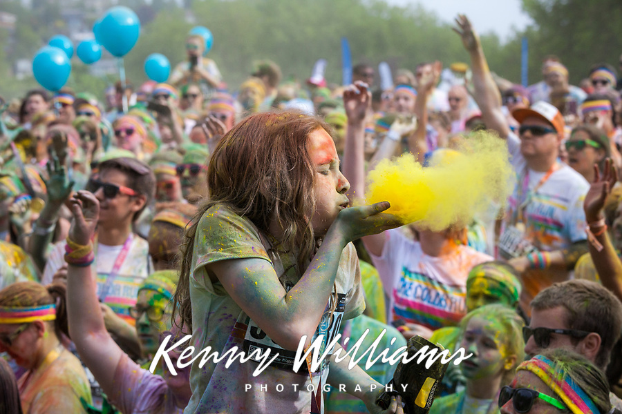 Girl Blowing Yellow Dye at The Color Run 2015 Music Concert, Seattle Center, Washington State, Wa, America, USA.