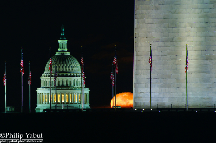 A waning gibbous moon rises near the U.S. Capitol dome.
