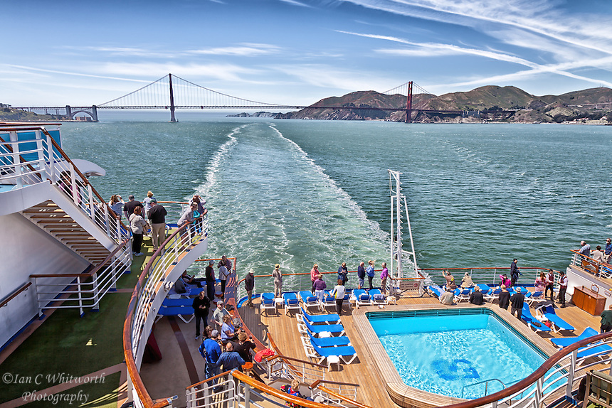 A scenic view or the Golden Gate bridge from the back of a cruise ship after sailing under the large span.