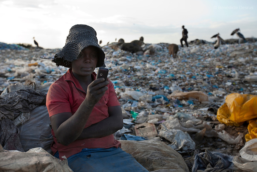 13 february 2013 - Dandora dumpsite, Nairobi, Kenya - A Kenyan woman check her cell phone at the Dandora dumpsite, one of the largest and most toxic in Africa. Located near slums in the east of the Kenyan capital Nairobi, the open dump site was created in 1975 and covers 30 acres. The site receives 2,000 tonnes of unfiltered garbage daily, including hazardous chemical and hospital wastes. .It is a source of survival for many people living in the surrounding slums, however it also harms children and adults' health in the area and pollutes the Kenyan capital. Photo credit: Benedicte Desrus