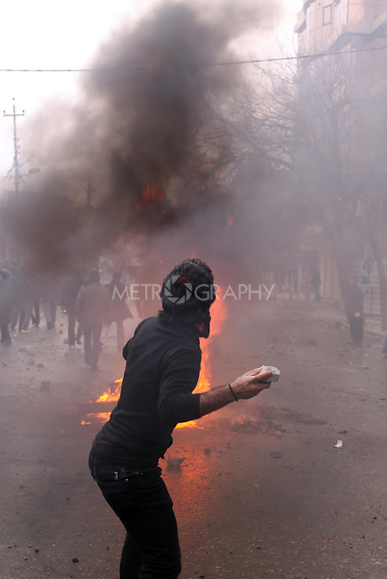 SULAIMANIYAH, IRAQ: A protester throws a rock at the police...A third day of violence rocks the Iraqi Kurdish city of Sulaimaniyah.  Tensions between protesters and security forces flare after the security forces continue to use life ammunition during the demonstrations...Photo by Aram Karim