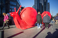 Giant snail sculptures on display in Columbus Circle in New York on Saturday, December 28, 2013. The exhibition by the REgeneration Art Project in collaboration with the Villa Firenze Foundation and the Galleria Ca' d'Oro in Rome features 8-foot giant red recycled-plastic sculptures created by the Cracking Art Group. The group, which consists of six artists, has a strong environmental and social commitment using recycled and recyclable plastic. The display will be on exhibit only until January 6, 2014 so better hurry! (© Richard B. Levine)