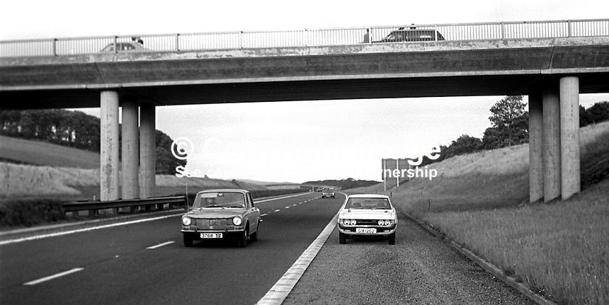 The section of the M2 where 17 year old  Henry Cunningham, a Protestant construction worker, from Carndonagh, Co Donegal, Rep of Ireland, was shot dead in a UVF gun attack on 10th August 1973. He was a front seat passenger in a minibus with a Rep of Ireland vehicle registration number. He was one of six workers, both Protestant & Roman Catholic, employed on a building site in Newtownabbey, on the outskirts of Belfast. Altogether 14 shots hit the minibus slightly injuring one other occupant. The Protestant paramilitary UVF would have assumed that all the occupants were Roman Catholic.  Police vehicles can be seen on the motorway bridge from which the shots were fired. 197308090541a..Copyright Image from Victor Patterson, 54 Dorchester Park, Belfast, United Kingdom, UK...For my Terms and Conditions of Use go to http://www.victorpatterson.com/Victor_Patterson/Terms_%26_Conditions.html