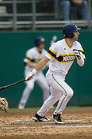 Michigan Wolverines outfielder Jackson Glines (27) follows through on his swing during the NCAA baseball game against the Washington Huskies on February 16, 2014 at Bobcat Ballpark in San Marcos, Texas. The game went eight innings, before travel curfew ended the contest in a 7-7 tie. (Andrew Woolley/Four Seam Images)