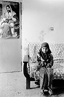 Iraq. Baghdad. Al Sadr City. Family Abo Basheer. The daughter sits on a couch. She wears a hijab on her head which covers her hair. A poster is taped on the door of Imam Ali. Shias regard Ali as the first Imam and consider him and his descendants the rightful successors to Muhammad. The word hijab (or hidjab) refers to both the veil covering the head and traditionally worn by muslim women (Islamic headscarf), but also the  modest muslim styles of dress in general. 20.02.04 © 2004 Didier Ruef