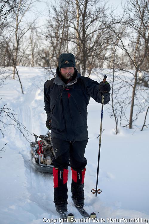 Mann har hentet et lass bjørkeved på pulken. ---- Man hauling firewood on sled.