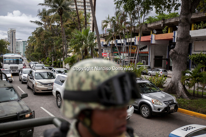 June 17, 2018: A Mexican army soldier keeps watching to the touristic boulevard as a military convoy surveil downtown Acapulco, Guerrero. A juncture of security forces, among them military, marines, federal police and local police joined under one-command to fight crime violence in the once-glamorous resort destination.