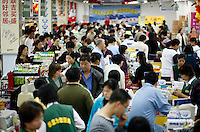 Shoppers go through the check out counters at a GSM Hualian Supermarket, one of several hypermarket chains owned by the Chinese retail conglomerate Shanghai Bailian Group in Shanghai, China..30 Oct 2006