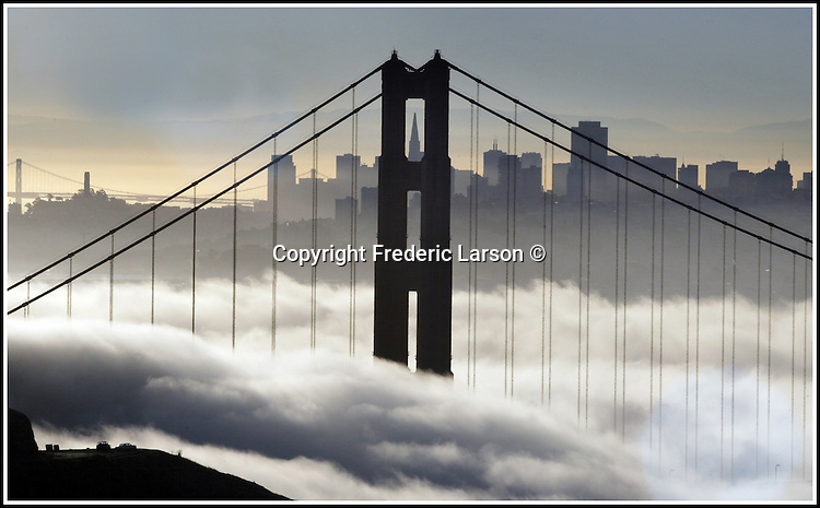 The fog rolls under the Golden Gate Bridge with the skyline of San Francisco in the background.