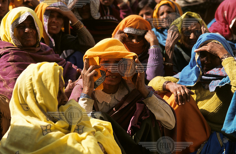 Women wait to have their sight tested at an eye camp..