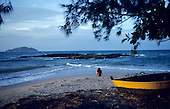 Buzios, Rio de Janeiro State, Brazil. Girl sitting on a beach looking out to sea with a small boat in the foreground.
