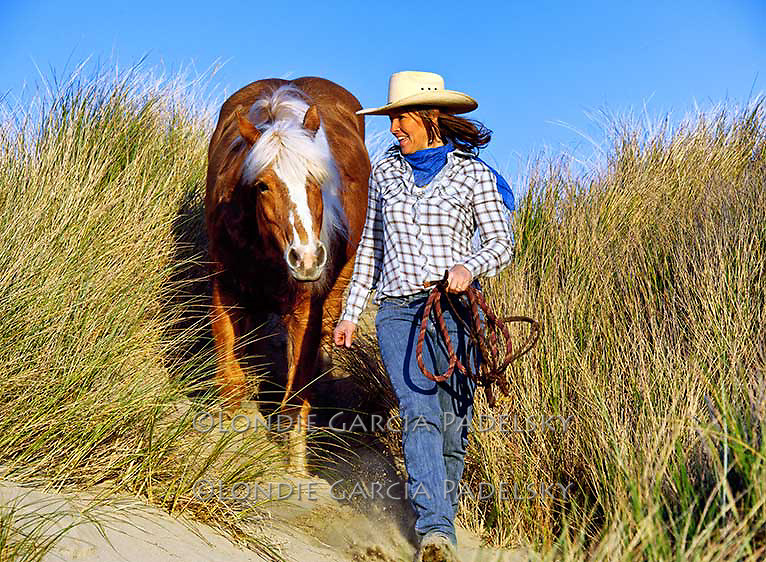 Cowgirl walking palomino horse on the sand dunes, Central Coast of California