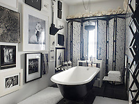 The walls of the black and white bathroom are lined with framed photographs and prints