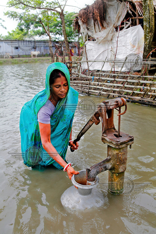 A woman pumps water from a well while standing knee deep in flood waters that have innundated the Satkhira district. Each year limited flooding helps to enrich the soil and create very fertile farm land. In turn, this results in a high population density on the flood plain. However, the low lying land is also prone to extreme flooding events that are very destructive and to both economy and life.