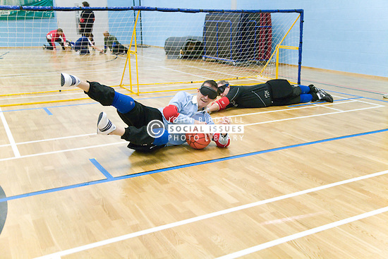 Team Player diving for the ball to stop it going into goal during a Goalball game; a threeaside game developed for the visually impaired and played on a volleyball court, A specially adapted ball containing an internal bell is used,