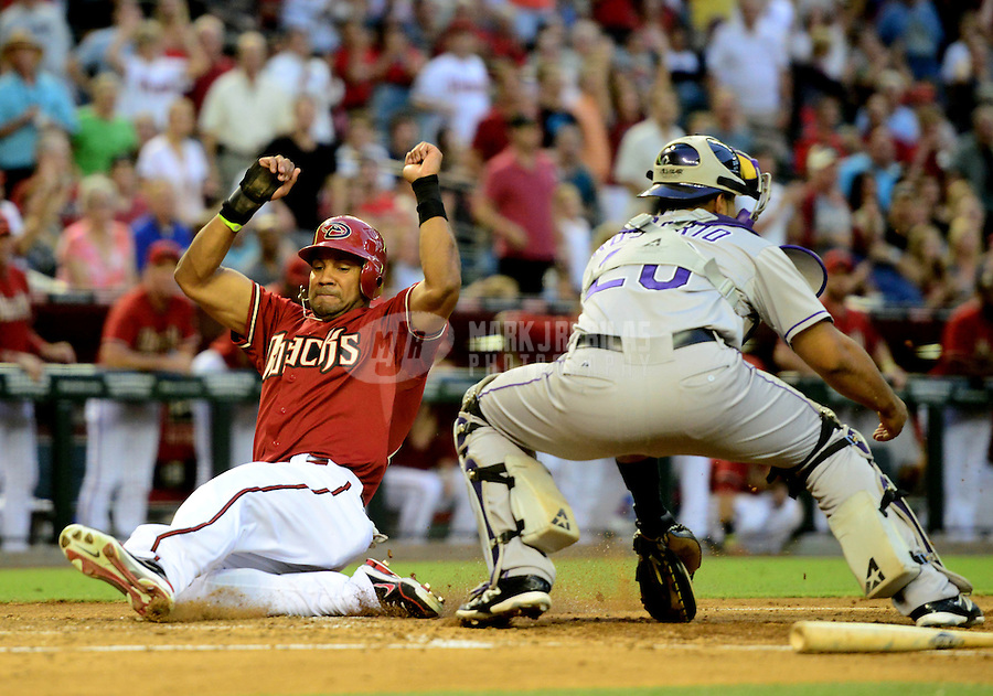 Jun. 6, 2012; Phoenix, AZ, USA; Arizona Diamondbacks base runner Chris Young (left) safely scores ahead of the tag by Colorado Rockies catcher Wilin Rosario in the third inning at Chase Field.  Mandatory Credit: Mark J. Rebilas-