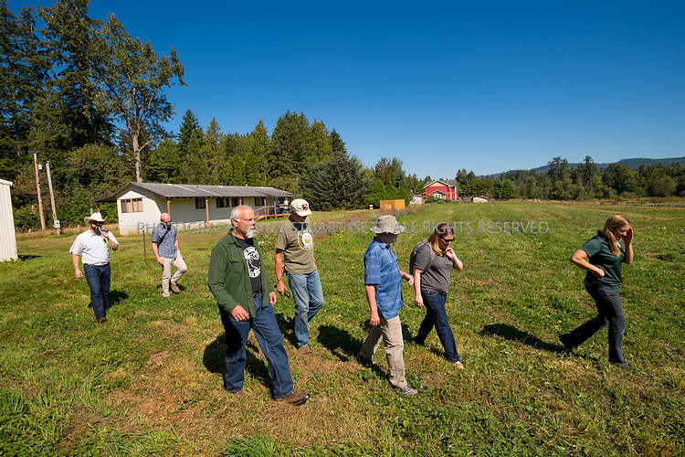 8/12/2016-- Mount Vernon, WA, USA<br /> <br /> Staff from the Schultz Family Foundation visit the Growing Veterans farm in Mt. Vernon, Washington, about an hour north of Seattle.<br /> <br /> Left to right:<br /> John  McCary (cowboy hat), Jason Raindorp , Kenny Holzemer,  Mike Hackett, Bill Smith, Liz  Willett (foundation),  Chris Wolf (woman).<br /> <br /> From http://growingveterans.org:<br /> <br /> &ldquo;Since 2012, Growing Veterans has been combining veteran reintegration with sustainable agriculture. Our unique model addresses the growing desire for alternative therapies for Post-Traumatic Stress (PTS) and Traumatic Brain Injury (TBI), as well as suicide prevention through peer-support and Applied Suicide Intervention Skills Training (ASIST) certification. We encourage continued service through volunteerism, and collective impact through collaboration with other local, regional, and national stakeholders.&nbsp; We provide opportunities for vets in transition to develop their resumes and identify how to translate skills learned in the military to new roles in the civilian sector. Further, our vets serve as leaders in the important movement toward sustainable agriculture&rdquo;<br /> <br /> Photograph by Stuart Isett. &copy;2016 Stuart Isett. All rights reserved.
