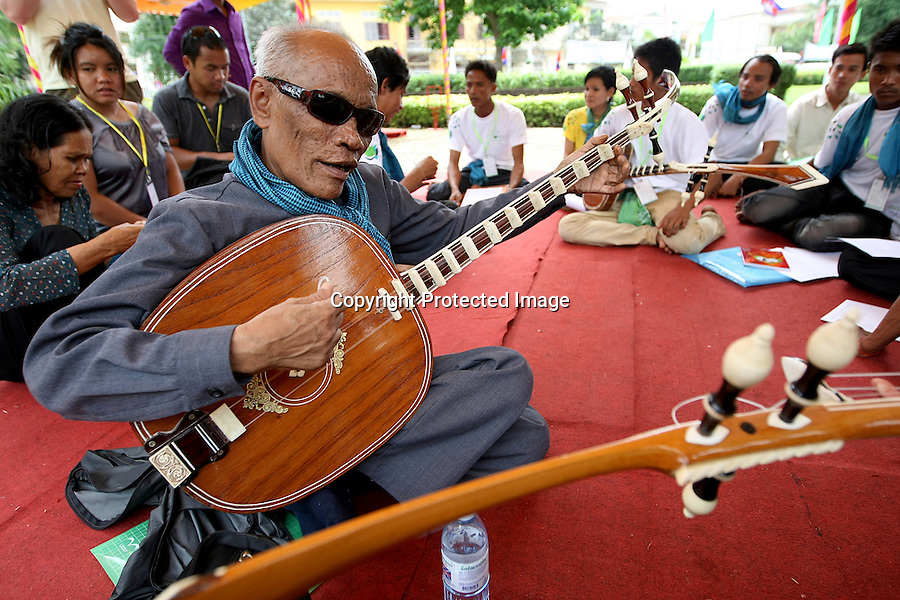 Cambodia Youth Arts Festival. Master Kung Nai, 65, during a workshop with students eager to learn Chapei Dang weng ( a long necked lute). Blinded by smallpox at the age of four, Kung Nai was miraculously spared from the Khmer Rouge regime's attempts to wipe out intellectuals and artists. Known as 'The Ray Charles of Cambodia', Master Kong Nai performed to international audiences and continues to play during religious cermonies in the Pagoda's of the Cambodian countryside. Phnom Penh, Cambodia-2010