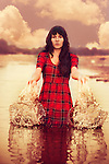 A young woman with long dark hair wearing a plaid dress standing alone in a lake splashing the water with her hands