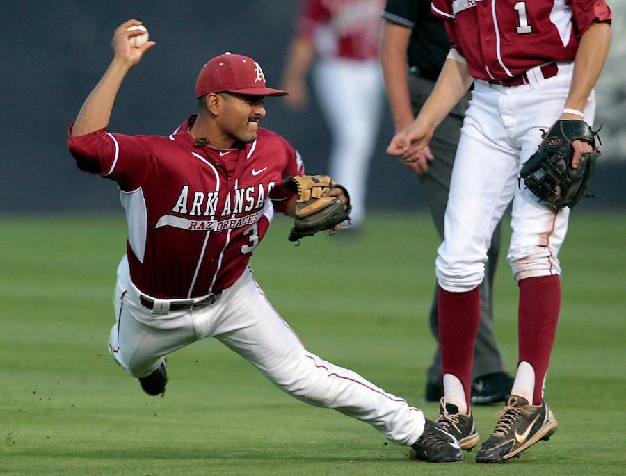 Arkansas infielder Michael Bernal (3) slips as he tries to throw to first base during the game against Virginia Saturday night at Davenport Field in Charlottesville, VA. Photo/The Daily Progress/Andrew Shurtleff