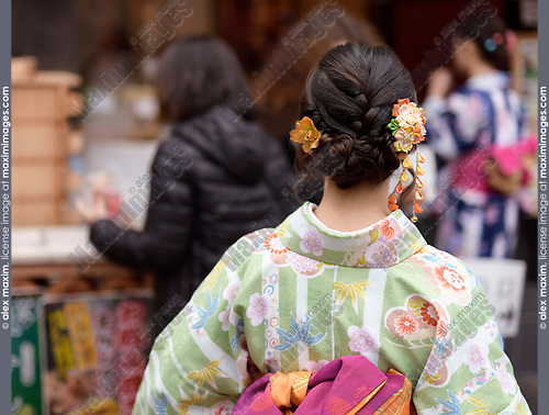 Japanese girl in colorful yukata kimono with a pretty hairstyle and intricate colorful hair ornament Kanzashi, rear view closeup. Kyoto, Japan.