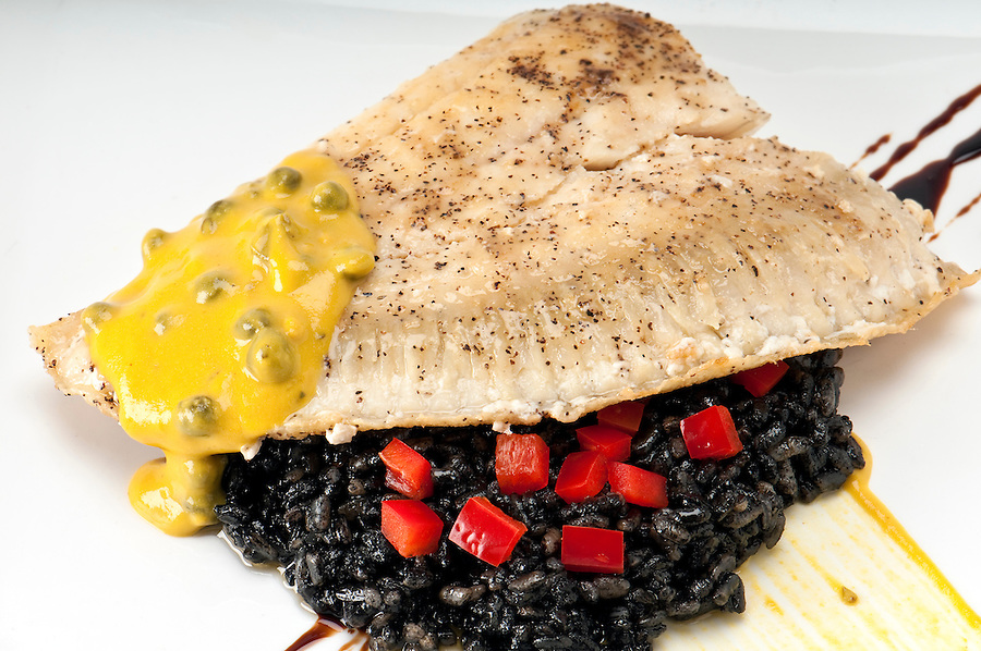 Close up of plate of halibut fillet over a bed of rice with squid ink, capers tomato and mustard.